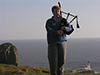 Thumbnail of Nat playing Bagpipes on a clif above the Neist Point Lighthouse